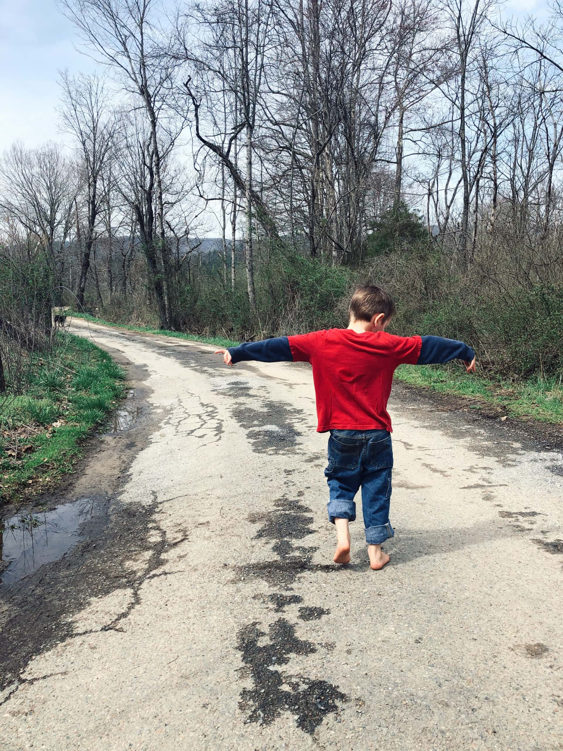 little boy walking down road with arms outstretched