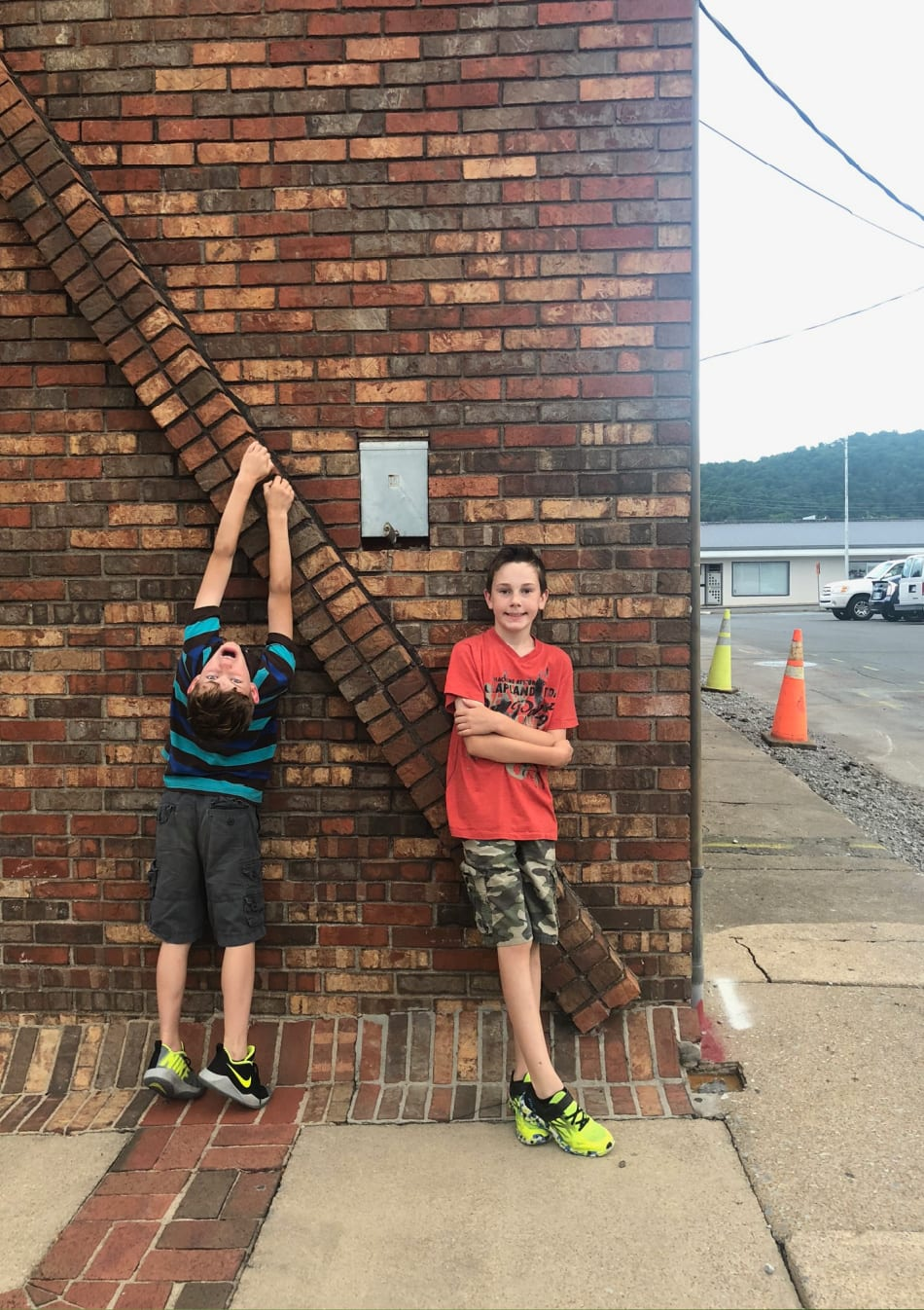 two boys next to a brick wall